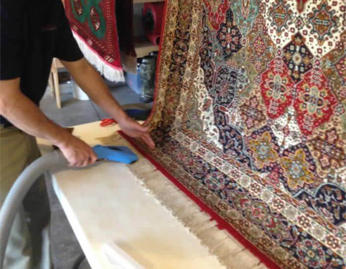 Magic Touch technician hand cleaning the fringe of an area rug.