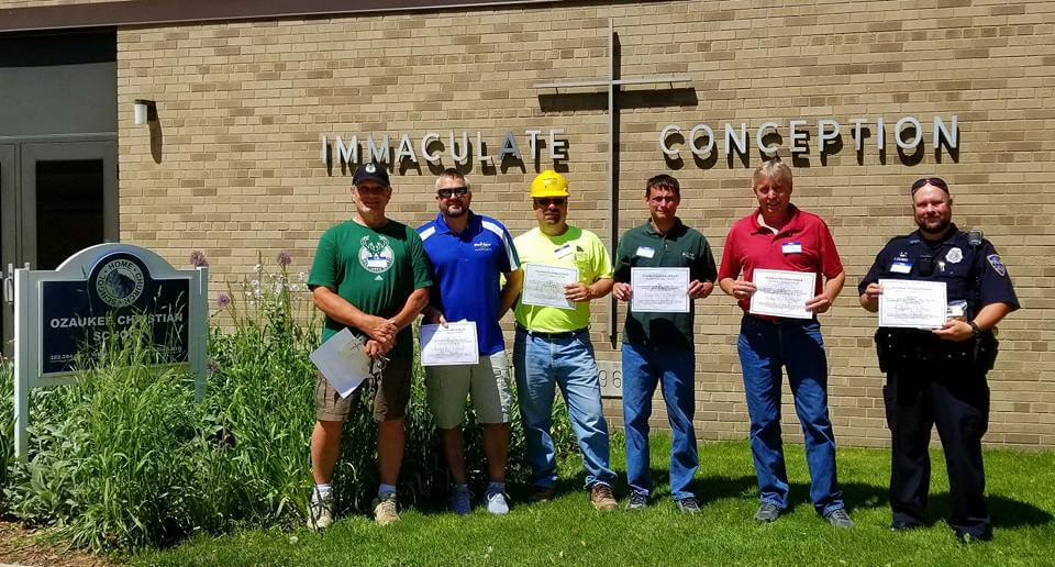 "Nick Kertscher (second from left), owner of Magic Touch Carpet Cleaning and Water Damage Restoration receiving the ""Character Quality Award"" from Ozaukee Christian School after tackling the school's flooding and water damage restoration in 2017."